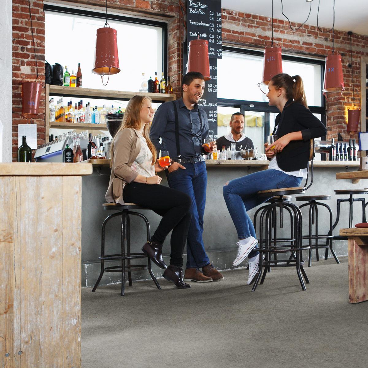 wineo Bodenbelag Designboden Grau Steinoptik Menschen in einem Café