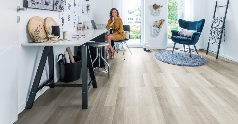 wineo Designboden mit Frau im Raum und eleganter Einrichtung