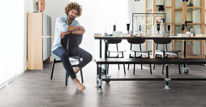 wineo Designboden mit Mann sitzend in der Küche mit Stuhl, Tisch und Schrank