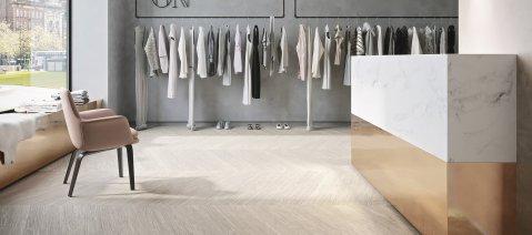 wineo Bodenbelag Holzoptik Fischgrätverlegung Modegeschäft Kleiderständer