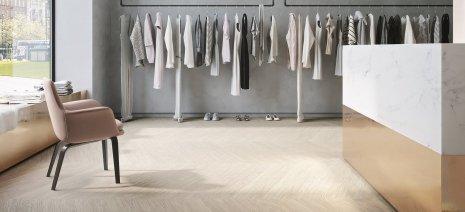 wineo PURLINE Bioboden Holzoptik Fischgrätverlegung Modegeschäft Kleiderständer