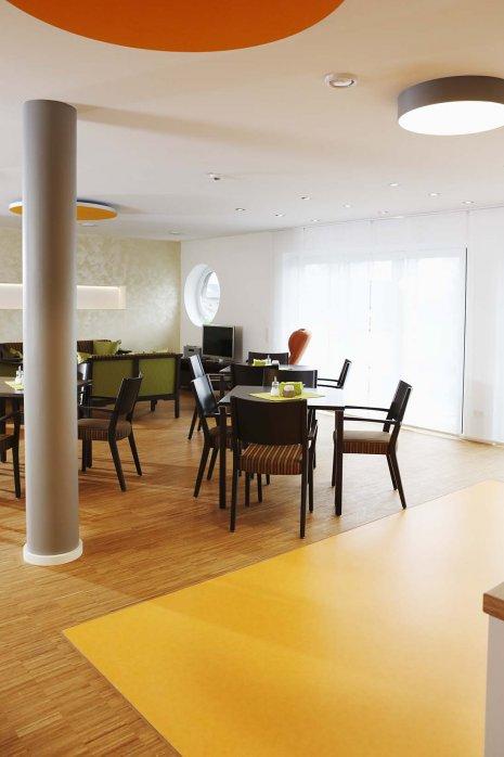 wineo PURLINE Bioboden im Altenpflege Bodeneblag grün Kantine Esszimmer Stühle Tische orange
